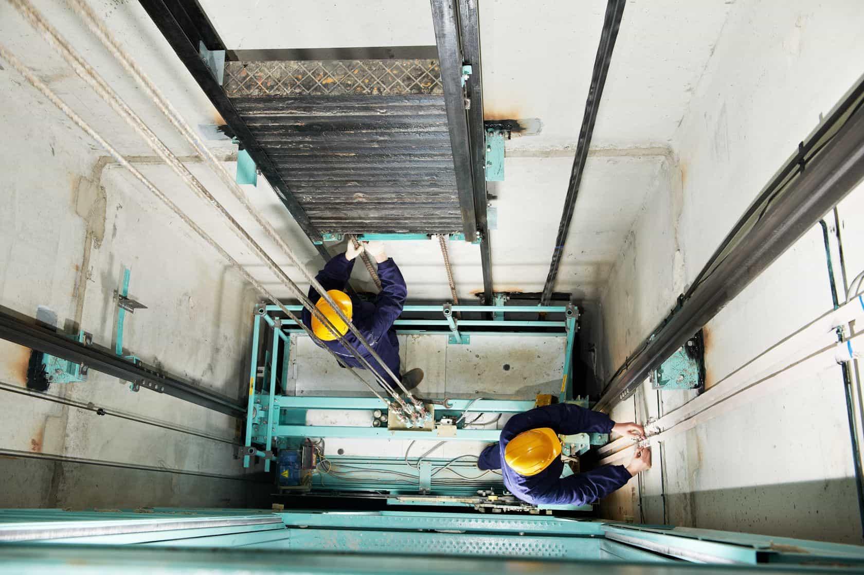 operarios en acciones de mantenimiento de un ascensor